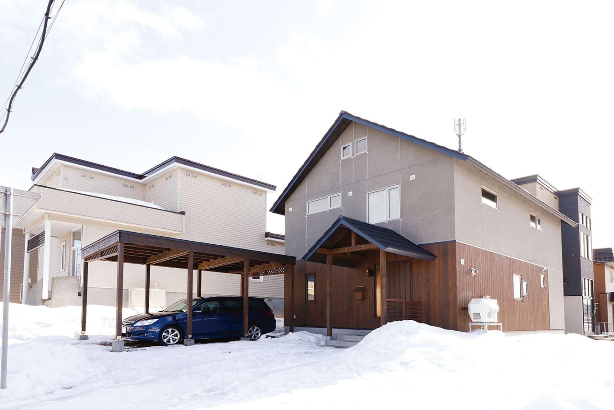 切妻の大屋根と、羽目板により木質感漂う1階の外壁が印象的なたたずまいを見せる外観 -  -  -