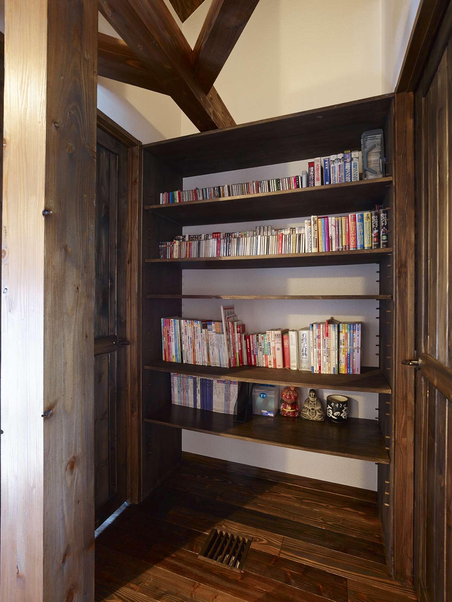 建具や床面と色をそろえて、2階ホールにも造作の本棚を設置 -  -  -