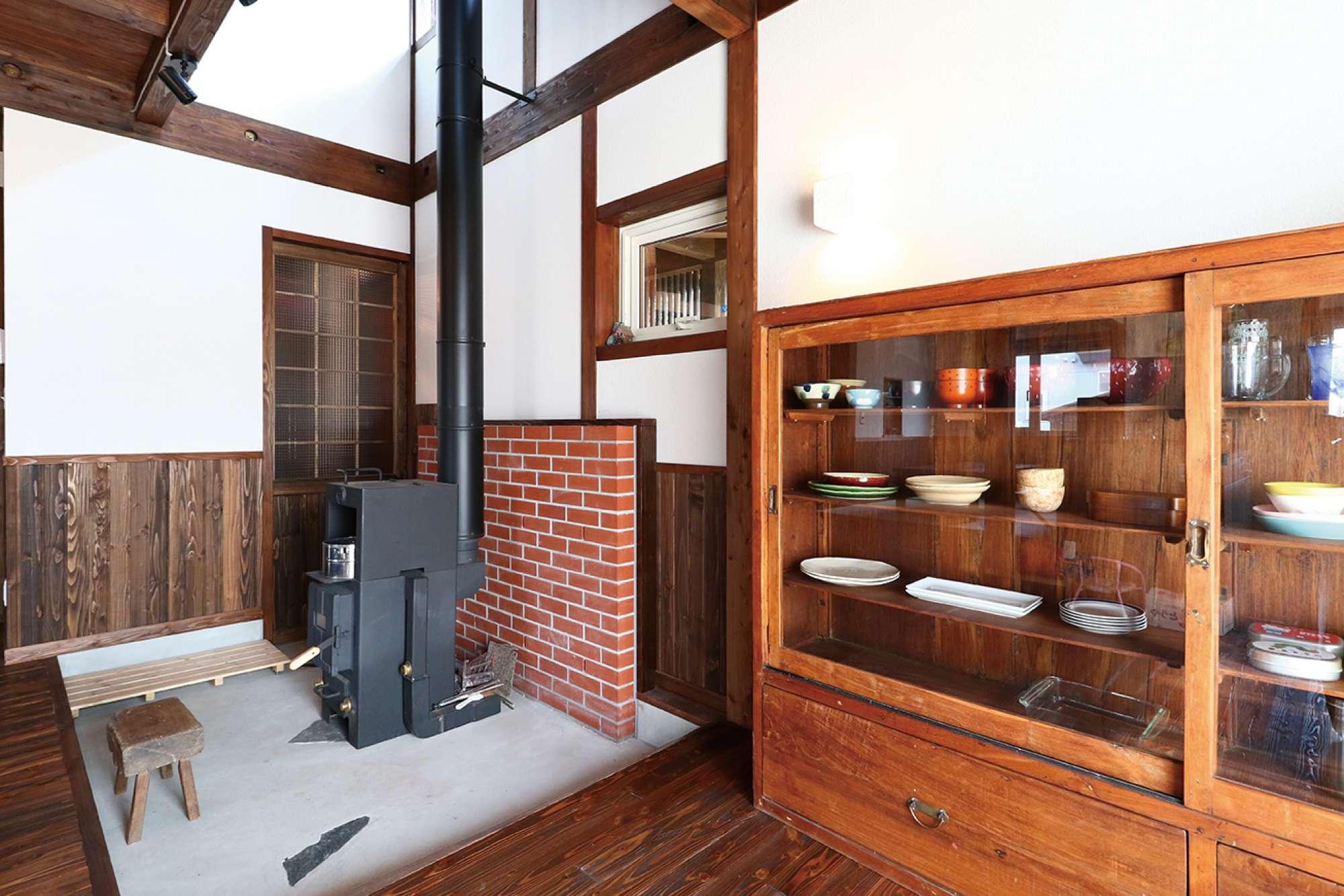 薪ストーブ背面のレンガを積み上げた壁が空間のアクセントに -  -  -