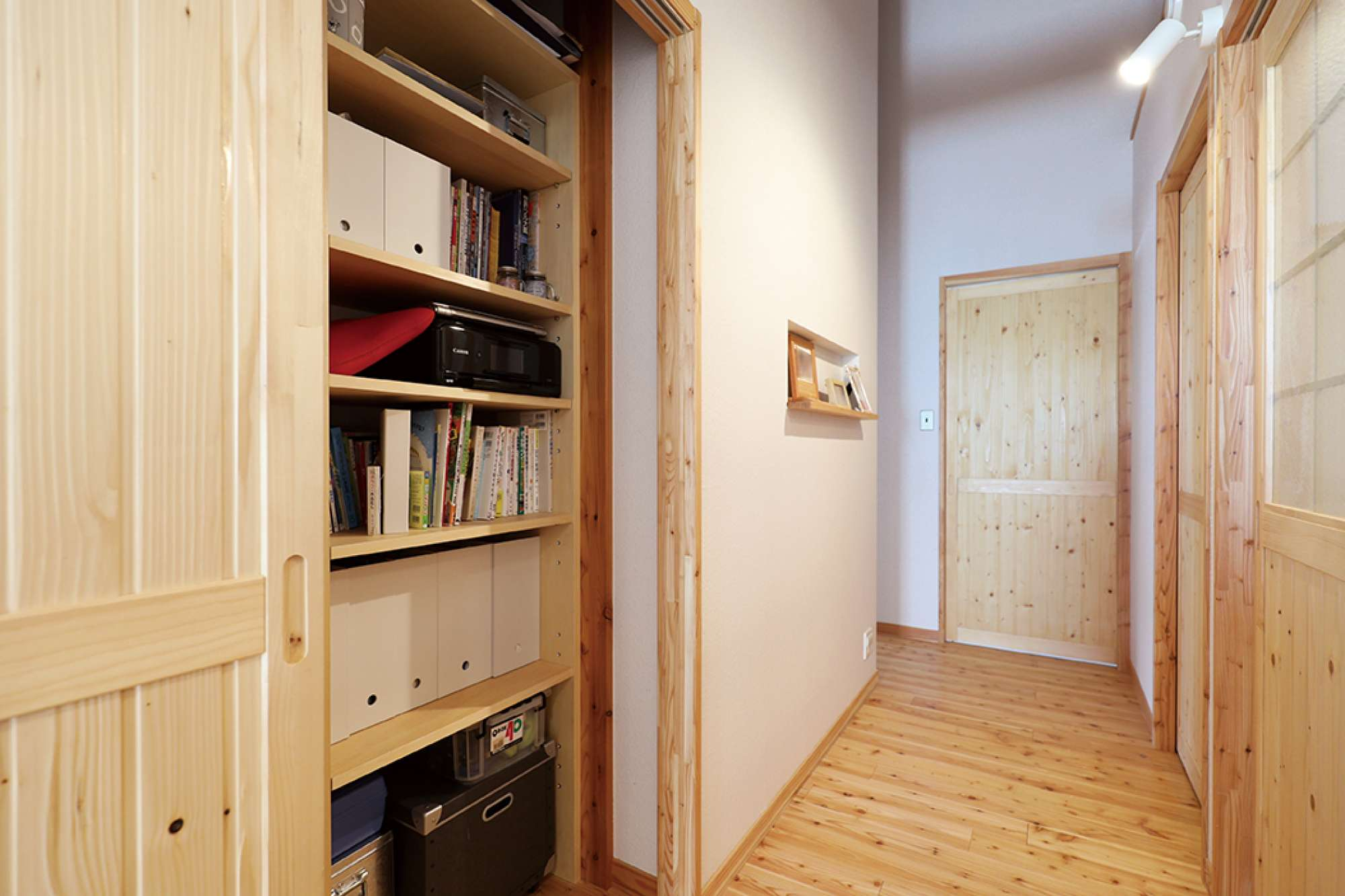廊下も木質感たっぷり。右は造作建具、左は棚付きの造作収納 -  -  -