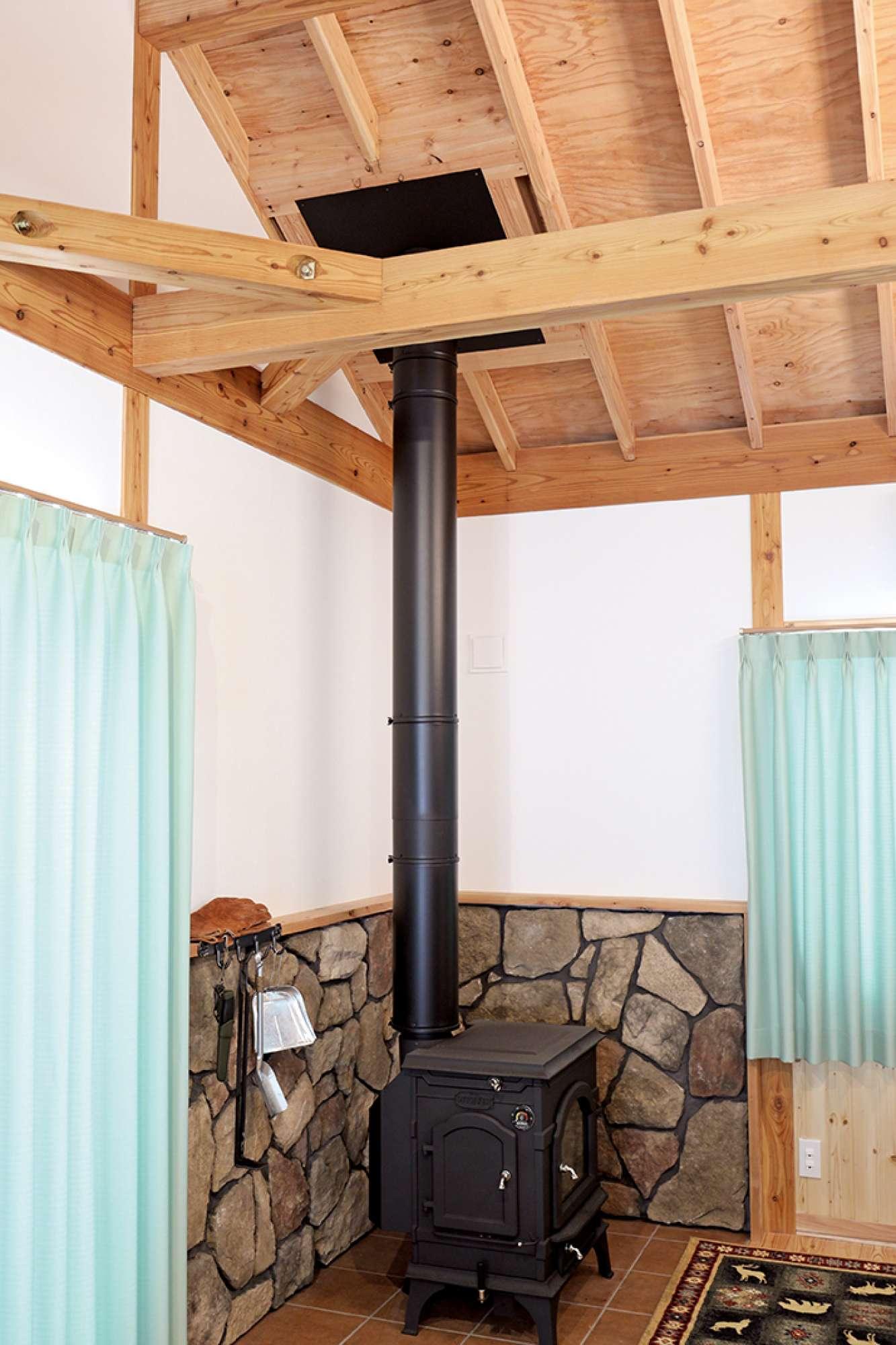 薪ストーブの背面壁は擬石でコーナーを演出、床はタイルを採用 -  -  -