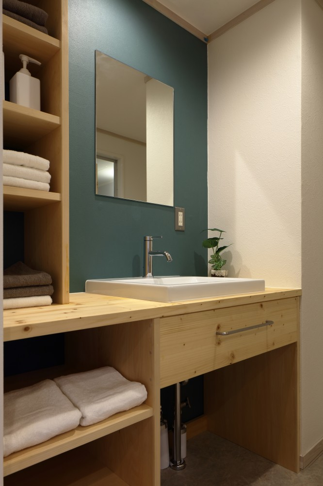 収納棚付きの明るい洗面台は正面のクロスがアクセント -  -  -